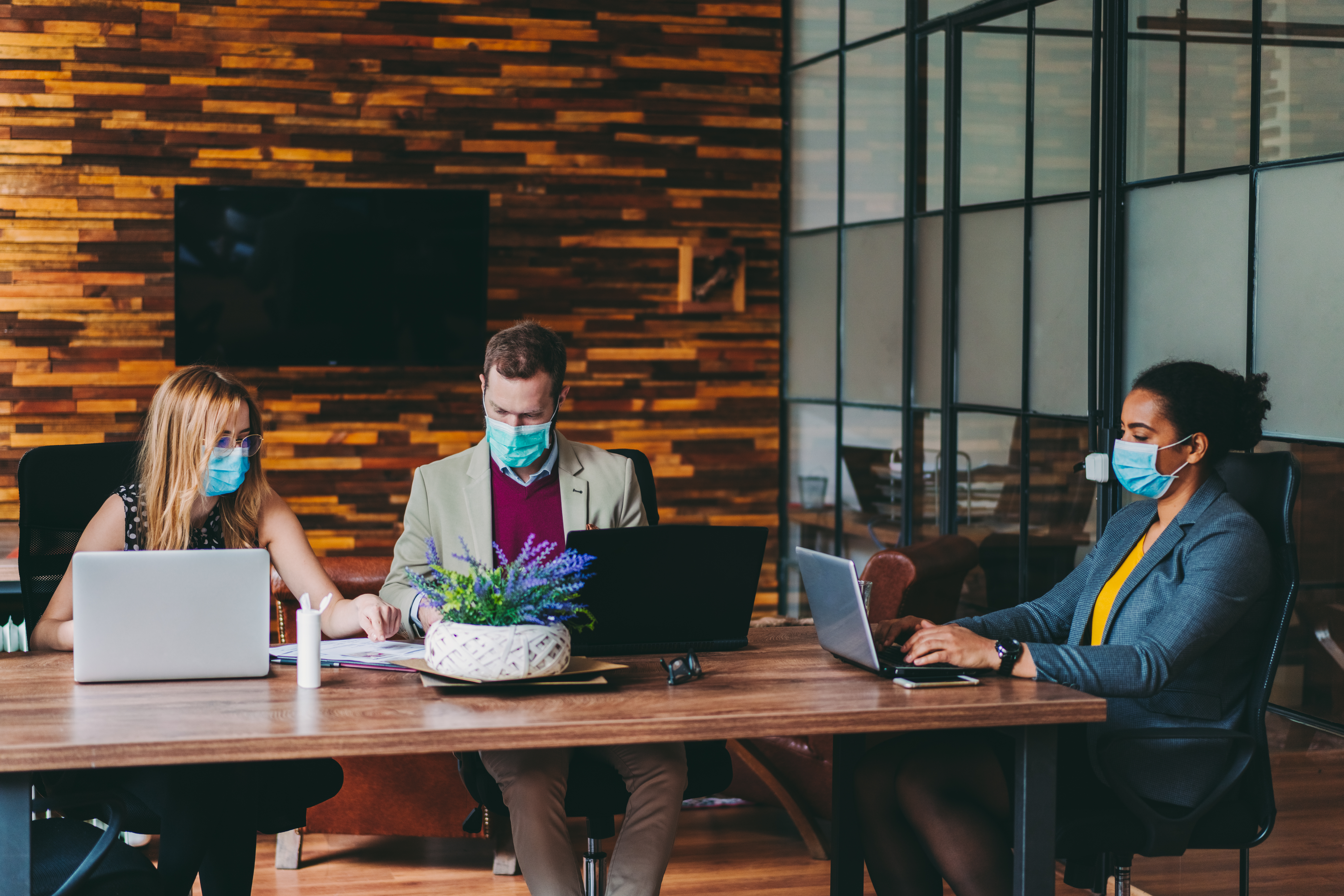 Business group at table with masks
