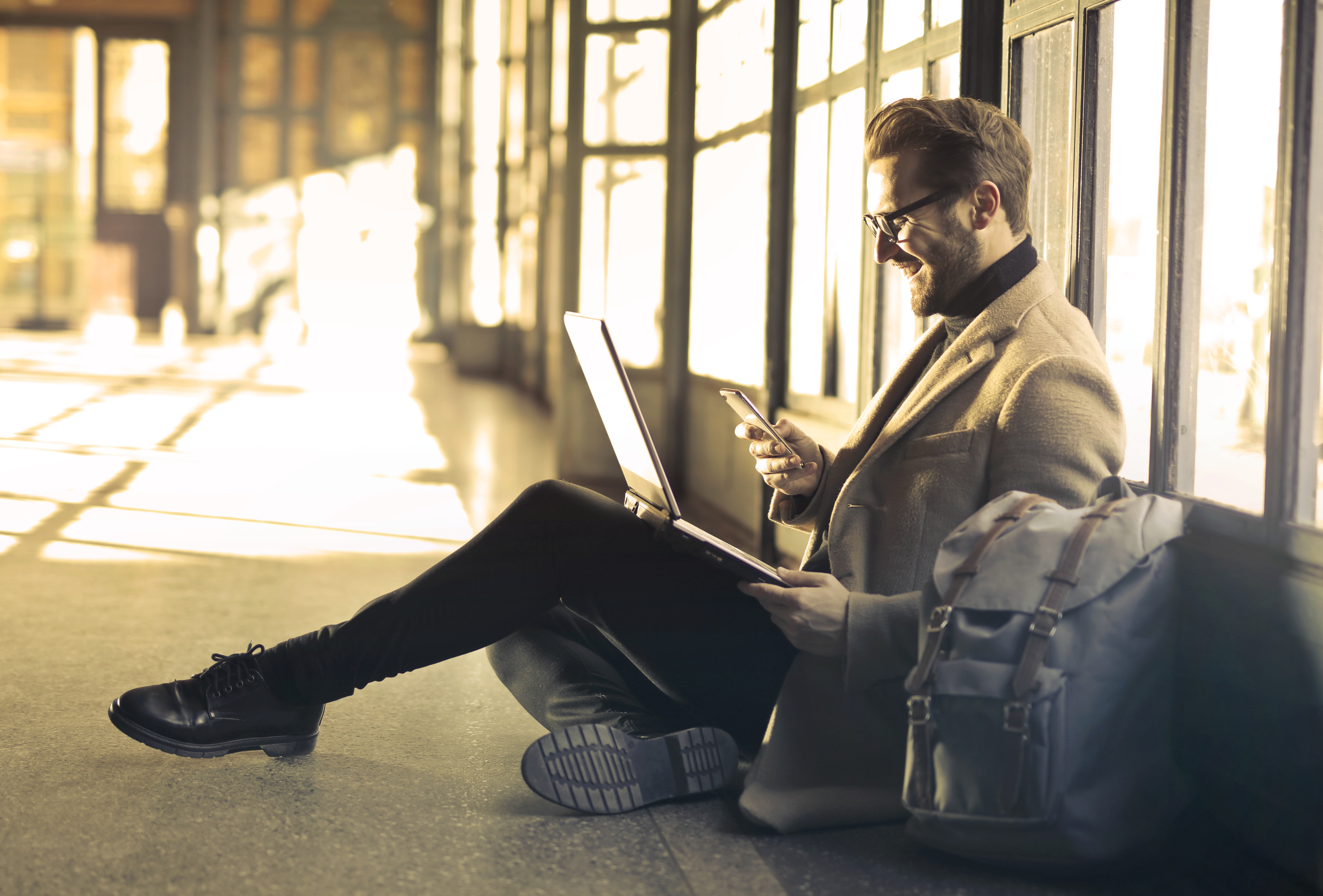 Man sitting on the floor checking email on his phone | Global Agency, BCD Meetings & Events