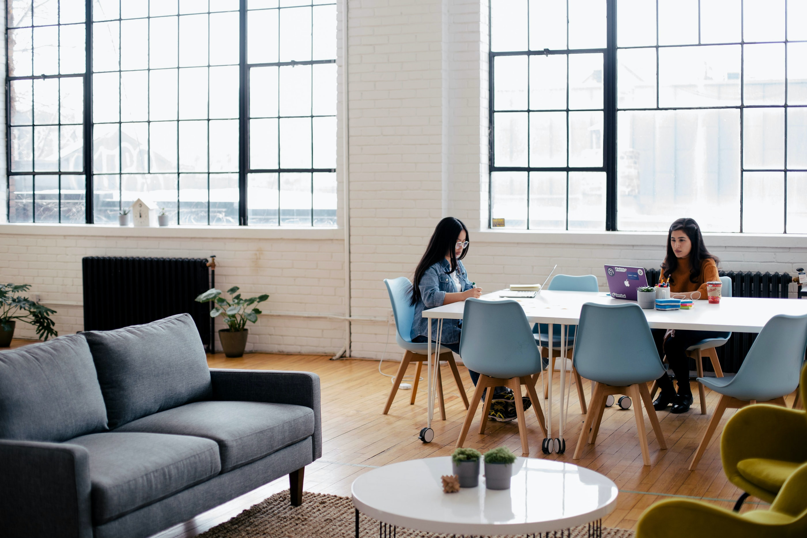 Two women sitting in break room joining virtual in-office speaker program   Global agency, BCD Meetings & Events