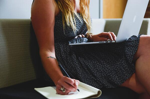 Woman writing while on laptop, working from home   BCD Meetings & Events