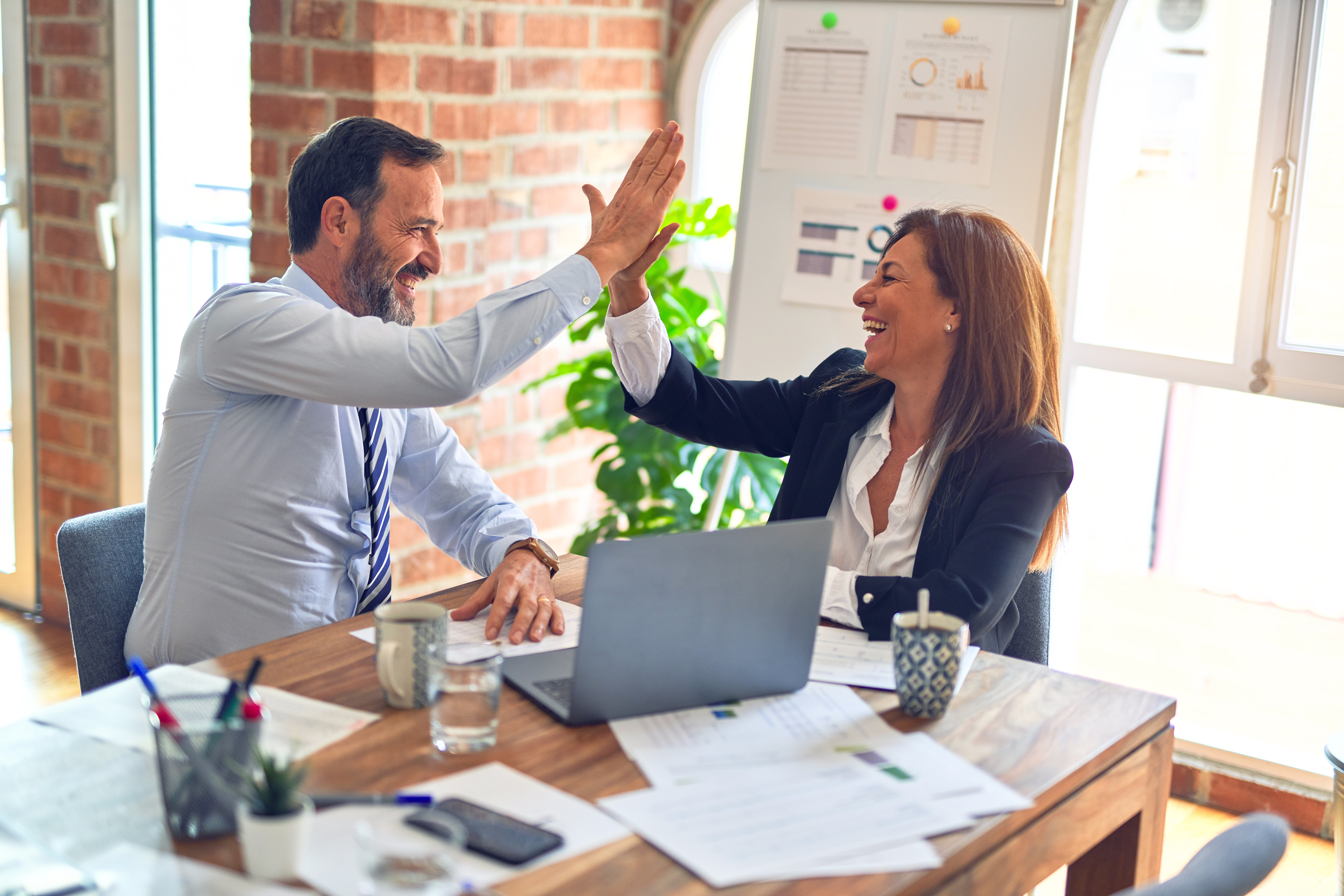 Two co-workers exchanging a high-five while working at desk | Global agency, BCD Meetings & Events