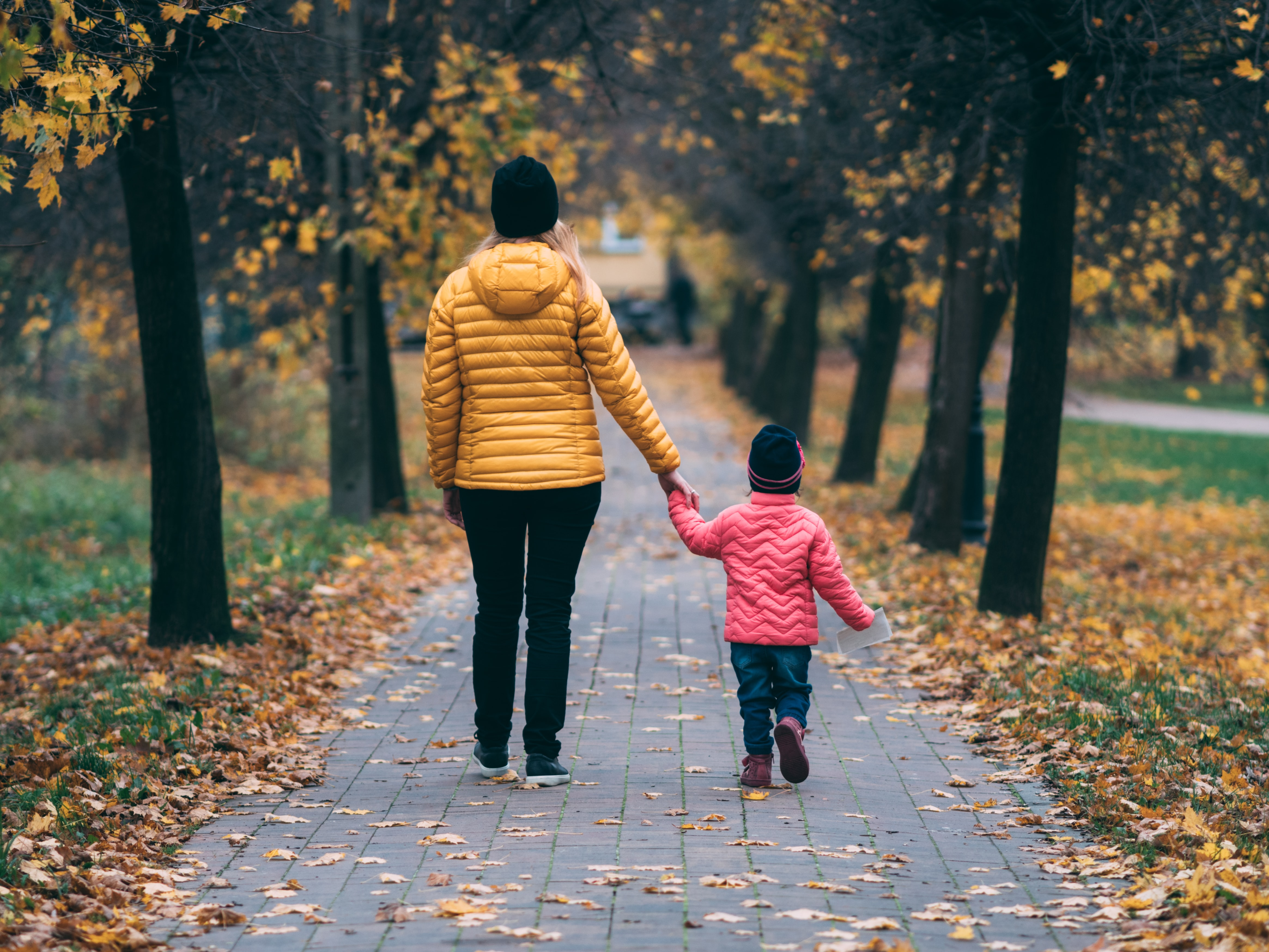 Woman holding hands with daughter walking outside | Global agency, BCD Meetings & Events