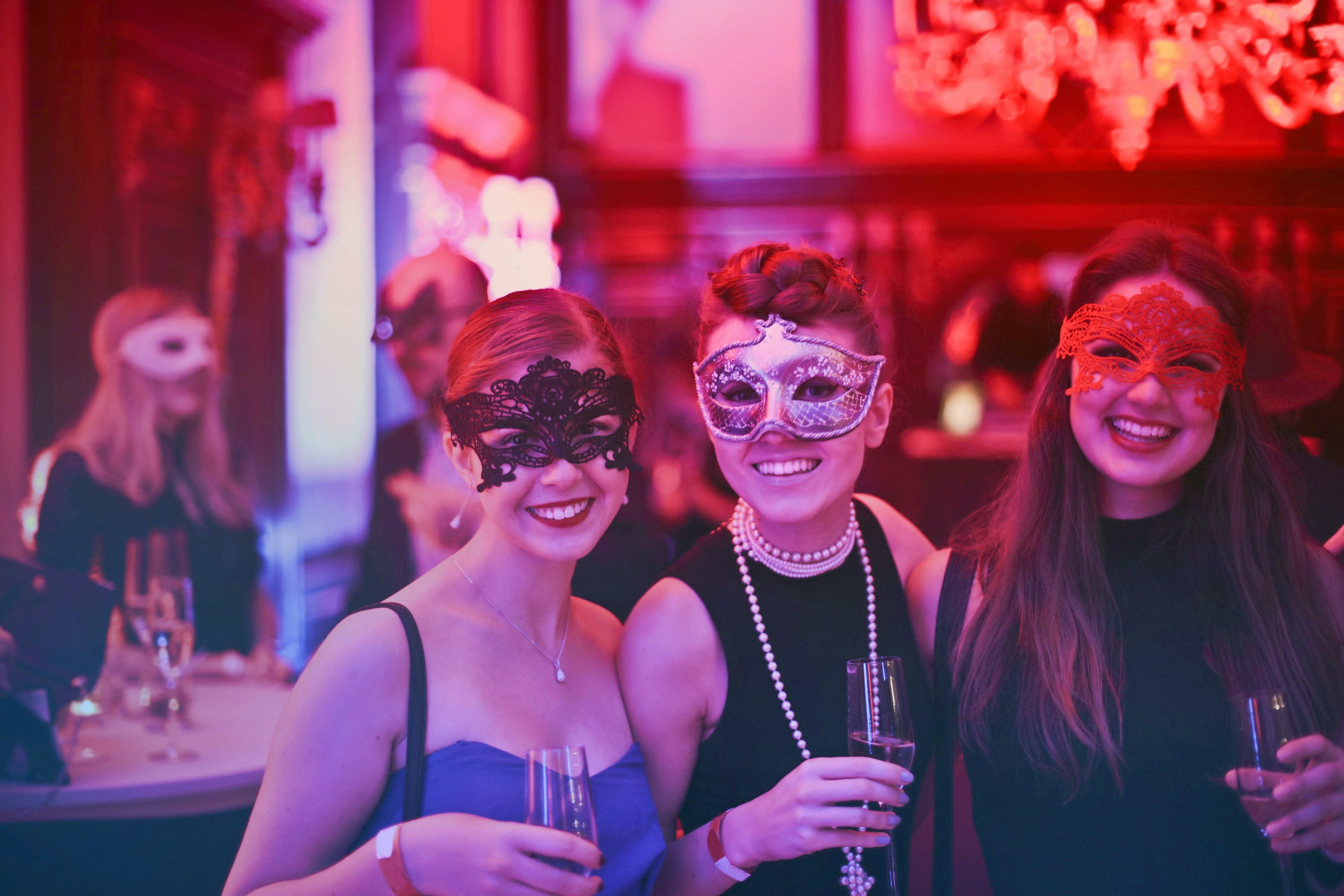 Group of three female event attendees, wearing masquerade masks at corporate event | Global agency, BCD Meetings & Events