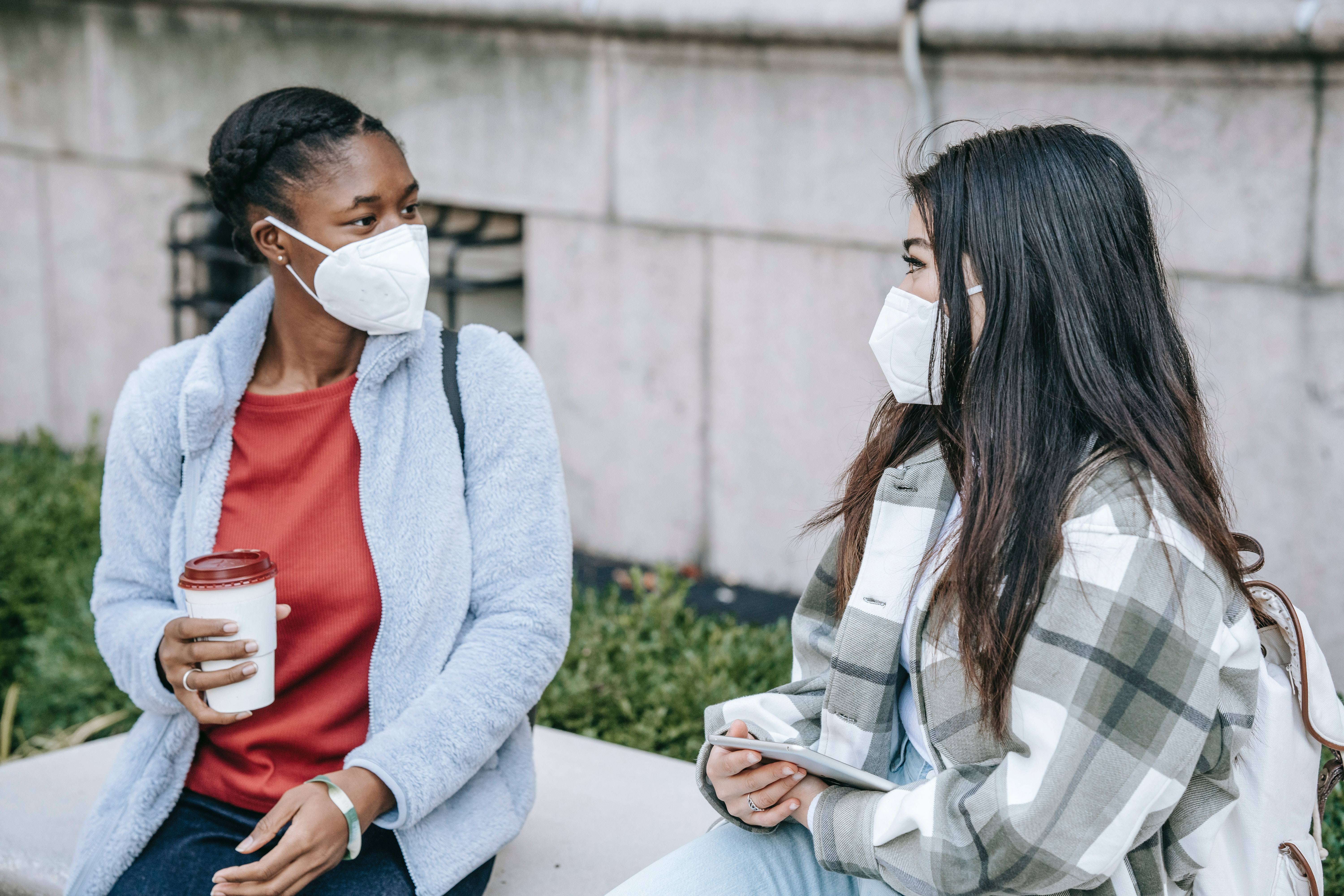 Two women sitting on a bench talking with masks on | Global agency, BCD Meetings & Events