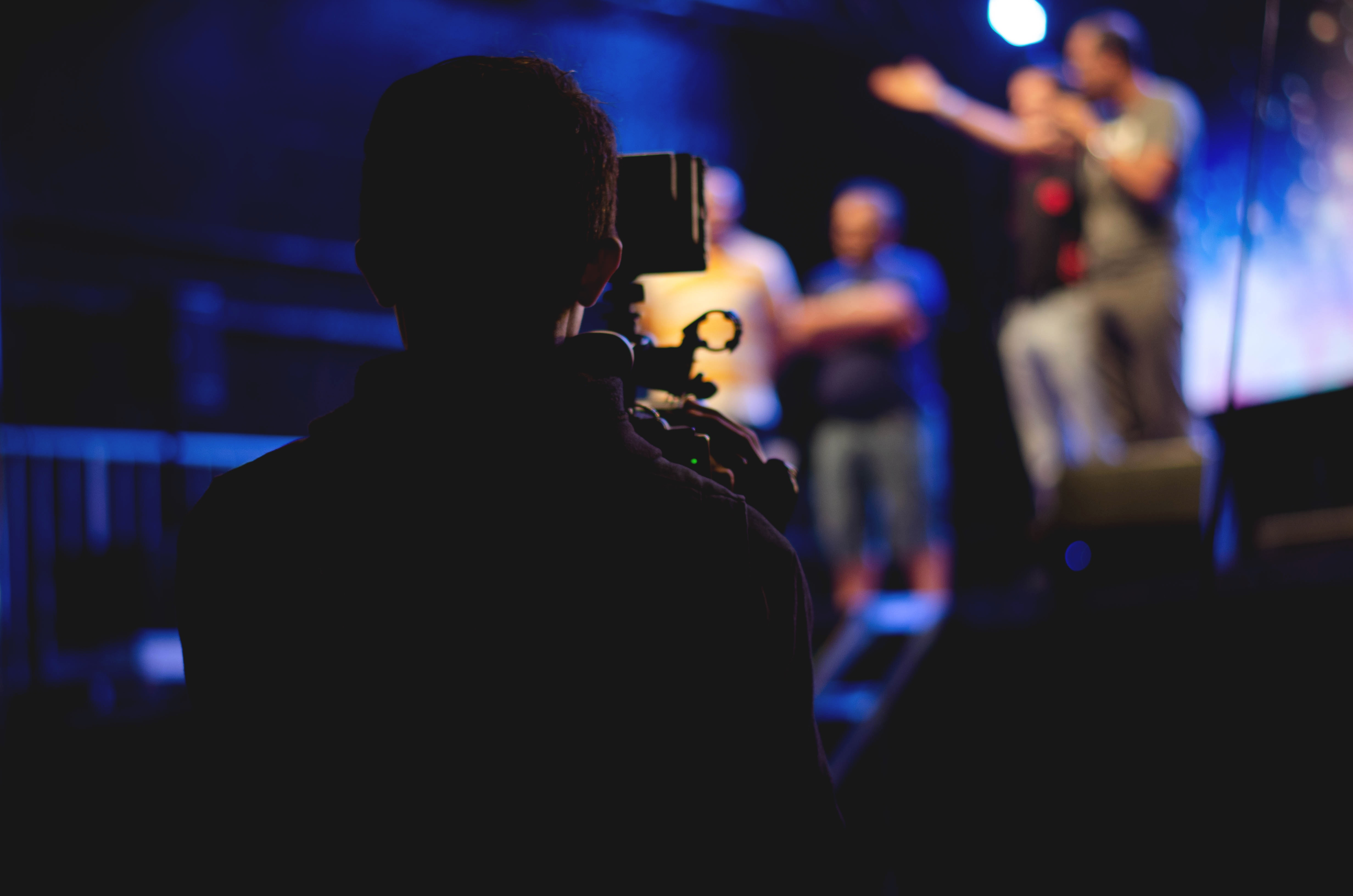 Man standing behind a camera filming presenters during live event | Global Agency, BCD Meetings & Events