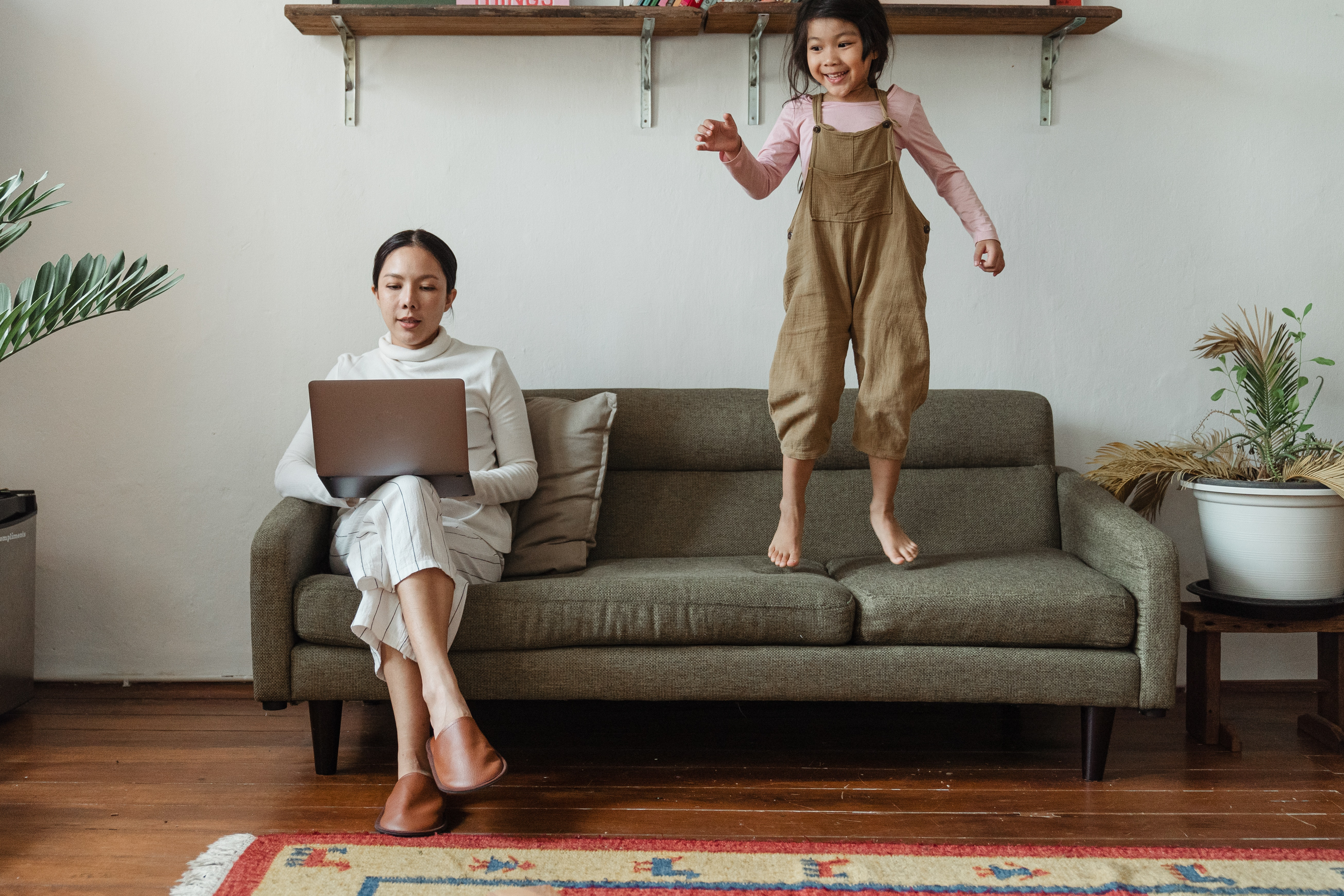 Woman on laptop participating in a Virtual Event at home while child jumps on couch | Global agency, BCD Meetings & Events