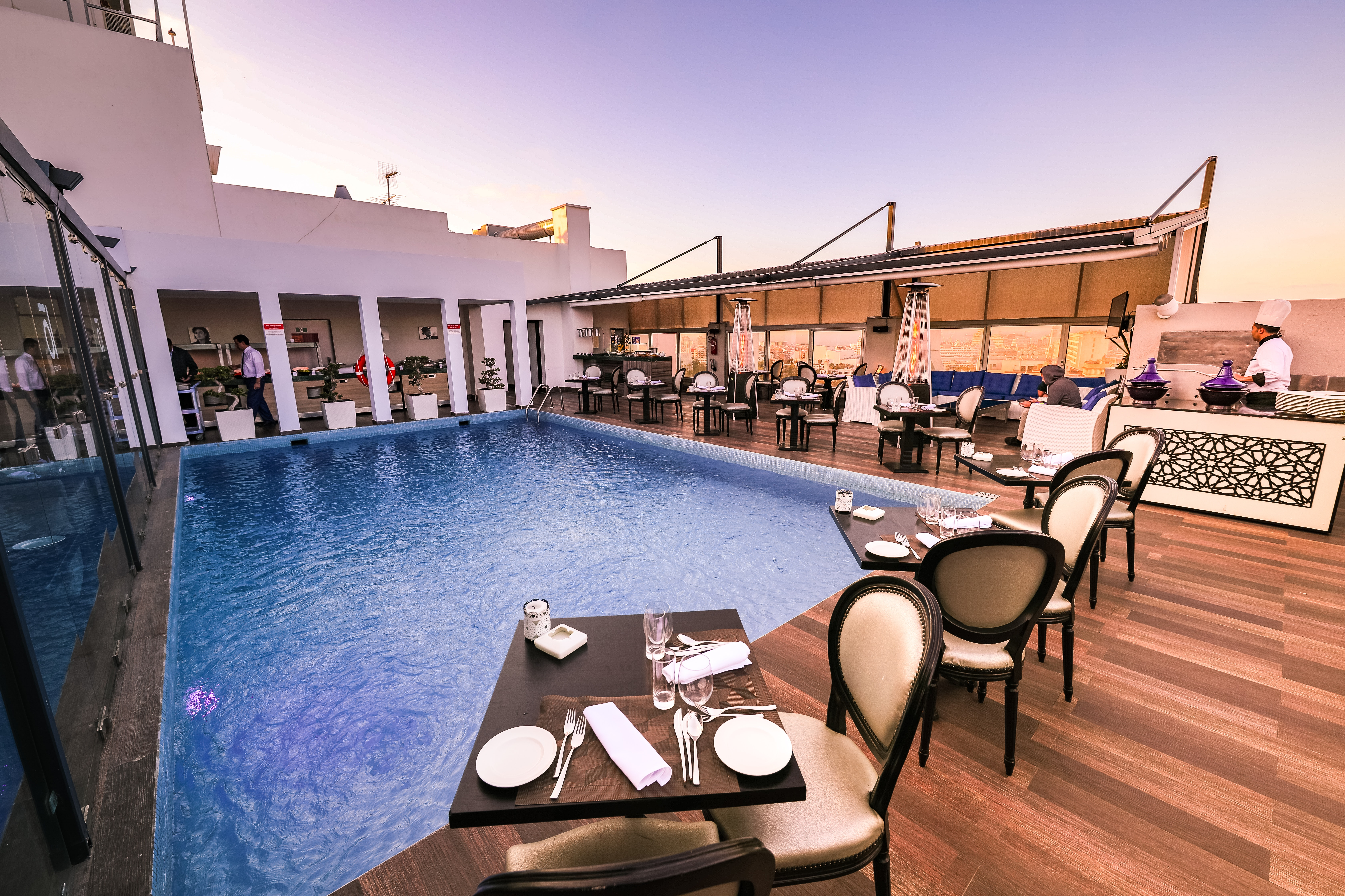 Dining tables set up around hotel pool as part of a corporate event   Global agency, BCD Meetings & Events