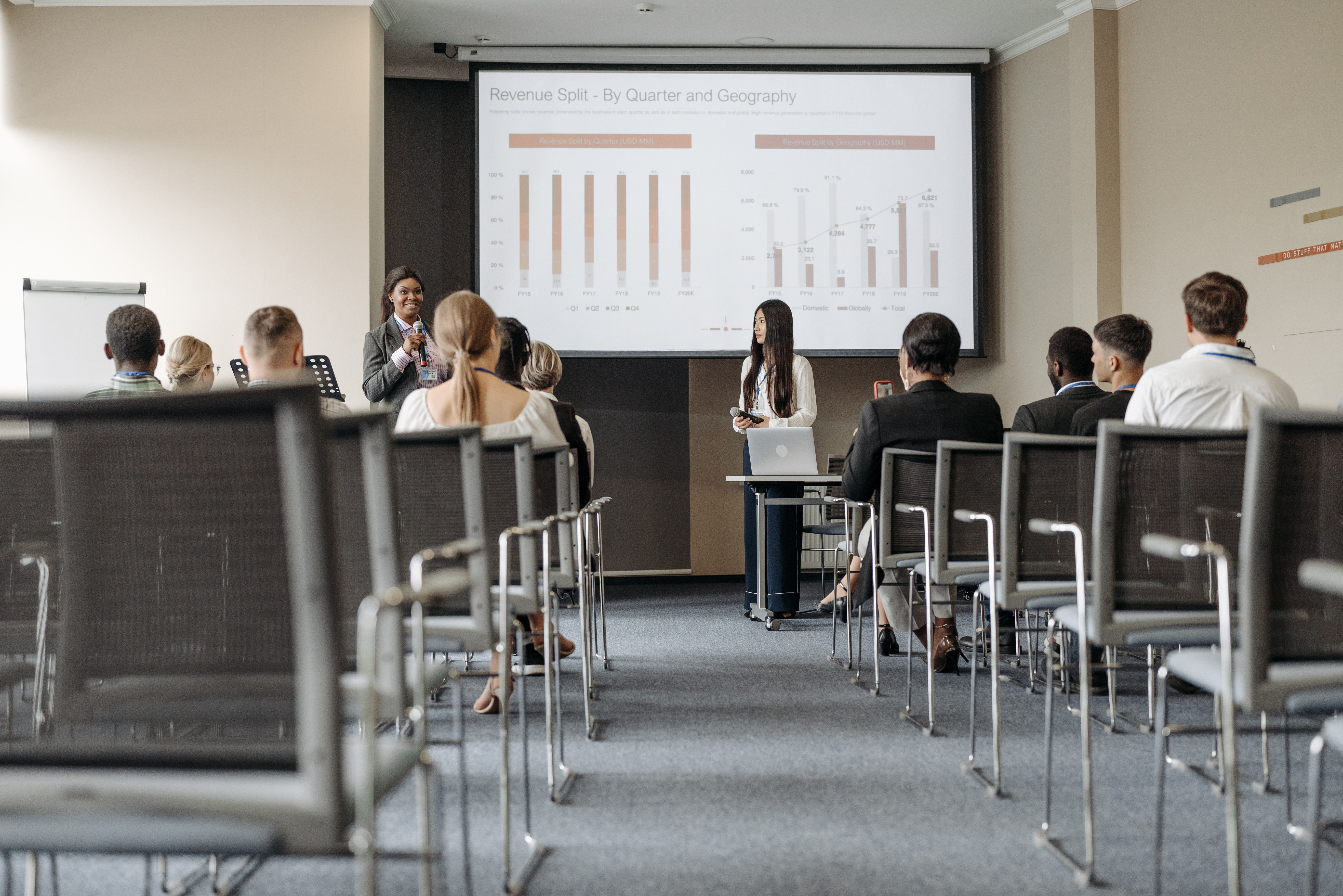 Two females speaking in front of an audience as part of a corporate meeting   Global Agency, BCD Meetings & Events