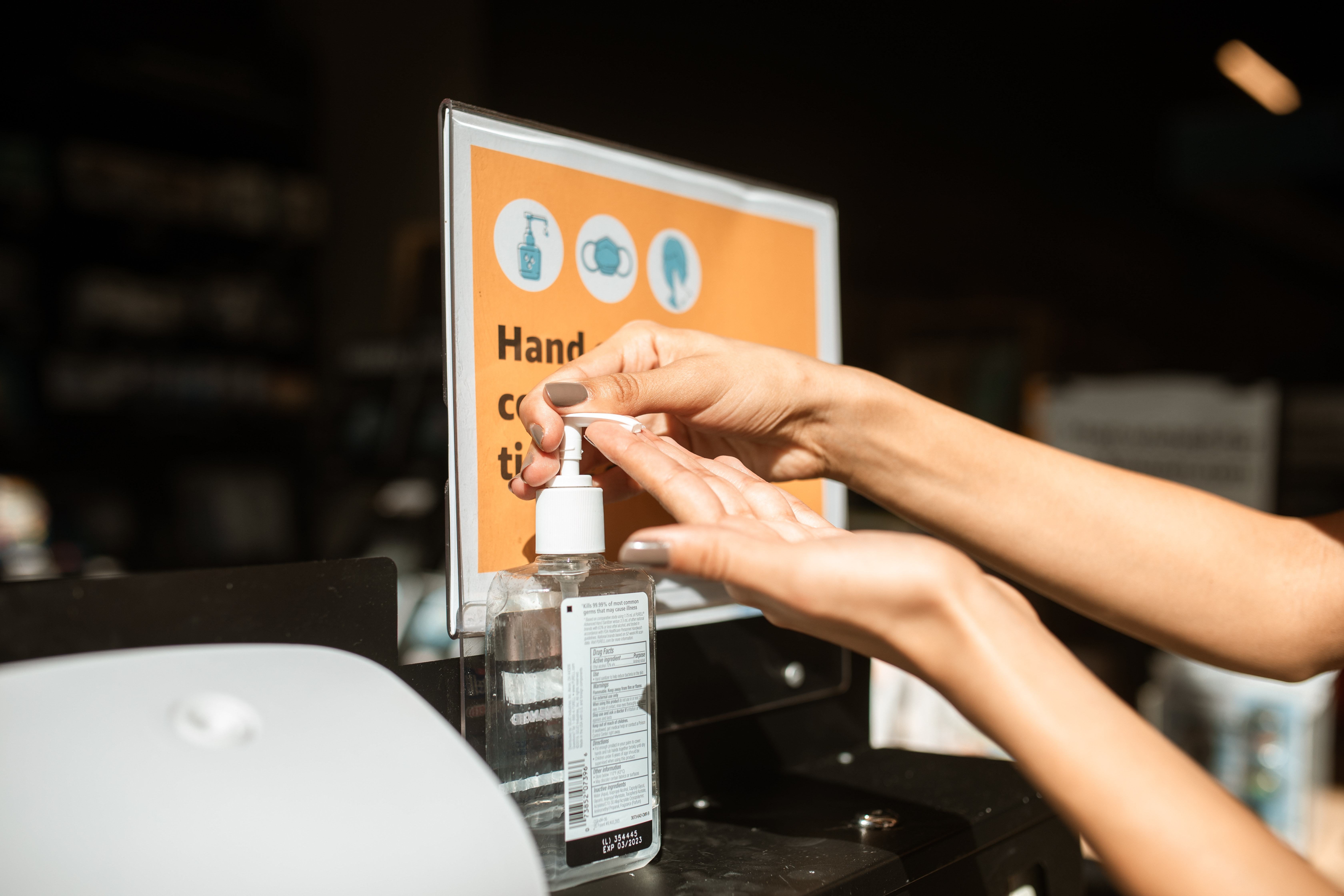 Person using hand sanitizer station at on-site event | Global agency BCD Meetings & Events