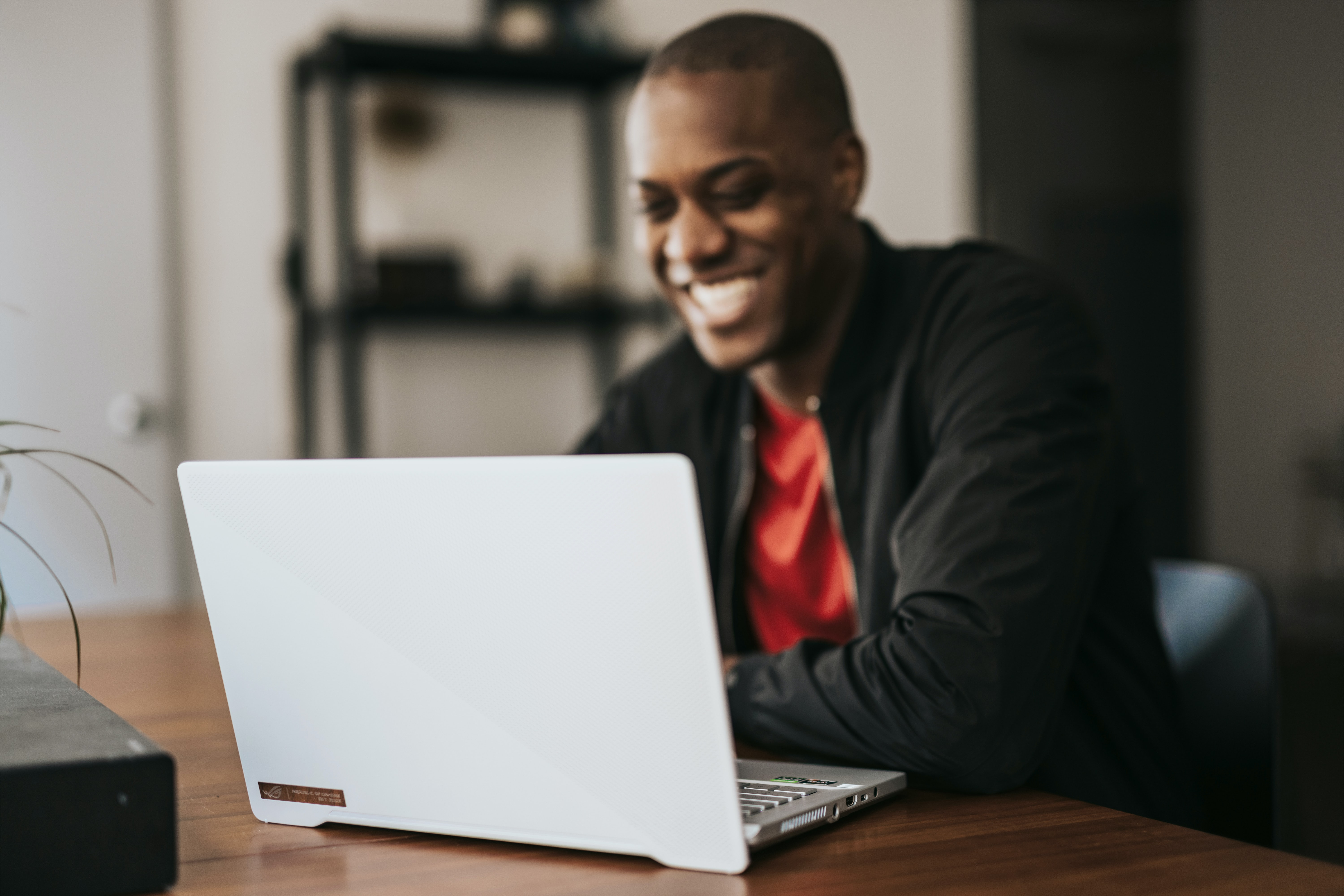 Man smiling while working on laptop | Global agency, BCD Meetings & Events